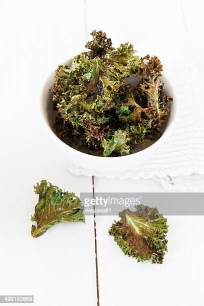 Bowl of curly kale chips on white wooden table