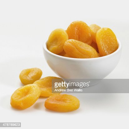 Bowl of dried apricots against white