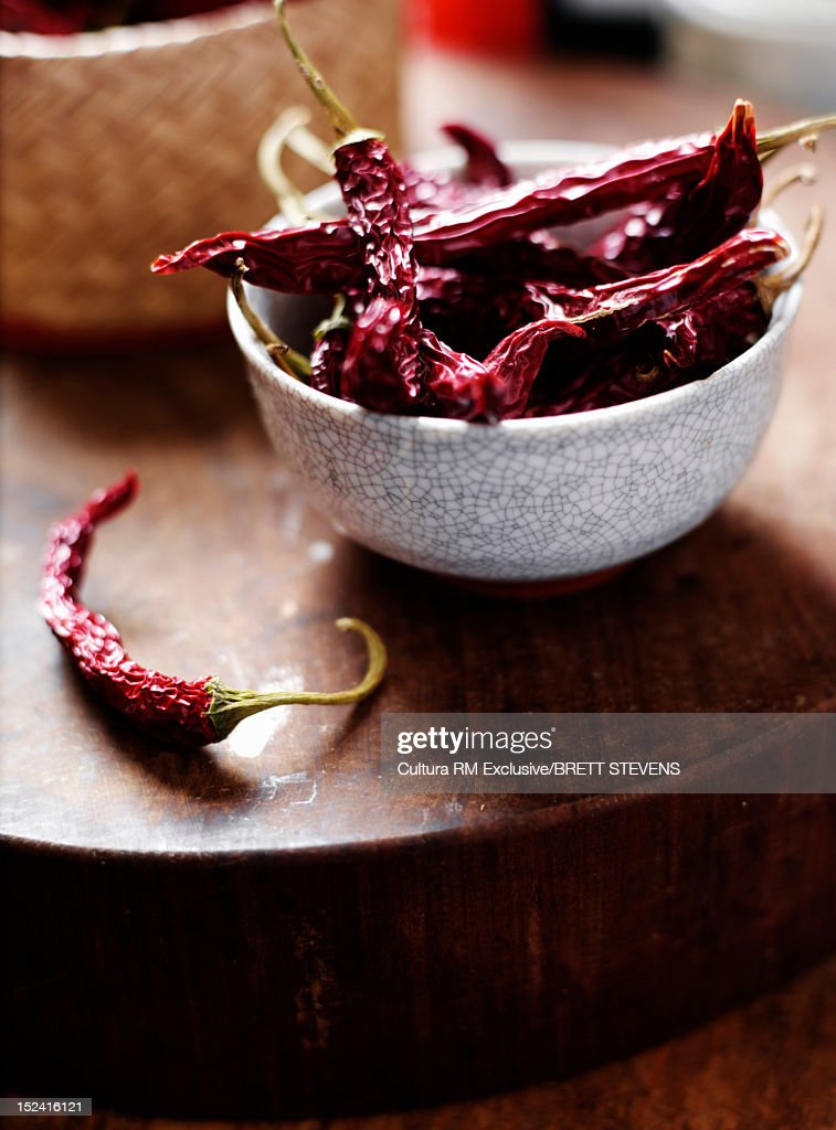 Bowl of dried chilis on wooden board : Stock Photo