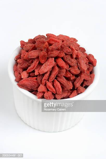 Bowl of dried goji berries, against white background, close-up