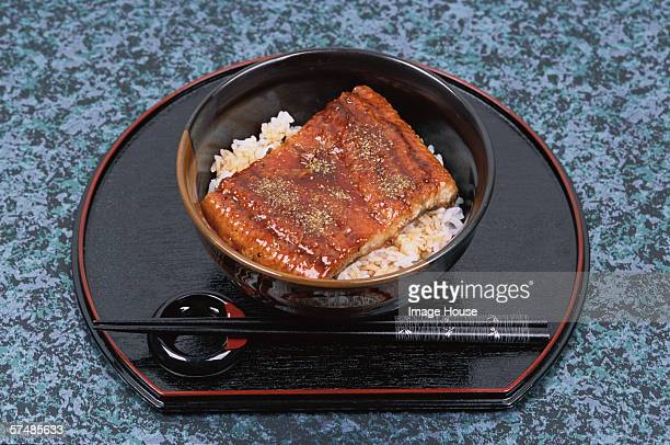 Bowl of eel and rice on tray (Unagi don), high angle view