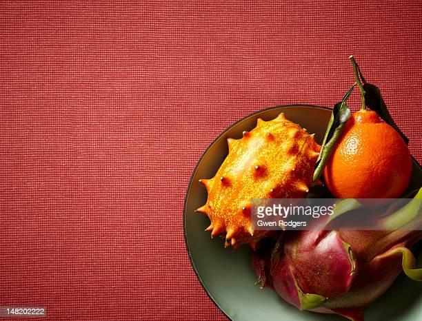 Bowl of exotic fruit on fabric background