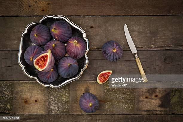 Bowl of figs and a knife on dark wood