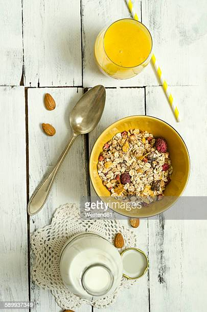 Bowl of fruit muesli, glass of mango smoothie, spoon and bottle of milk