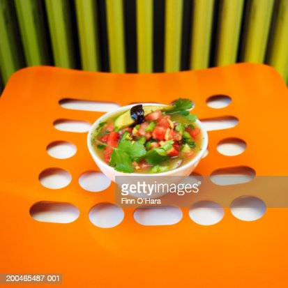 Bowl of gazpacho on orange place mat : Stock Photo