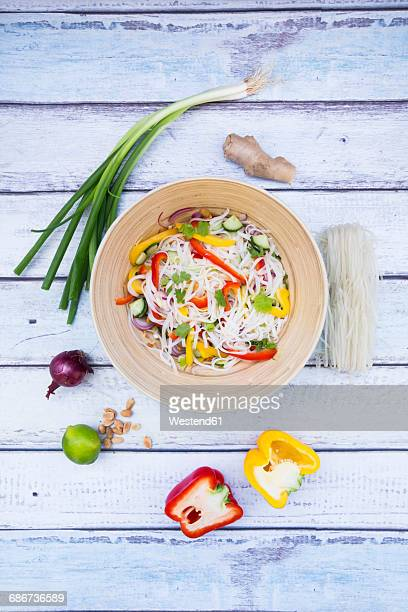 Bowl of glass noodle salad with vegetables and ingredients on wood