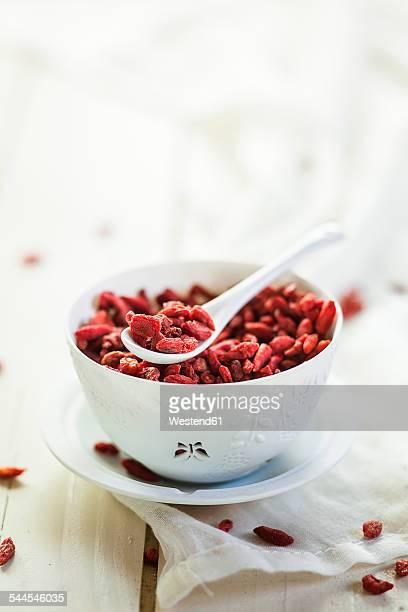Bowl of Goji berries, Lycium barbarum, on kitchen towel and wood