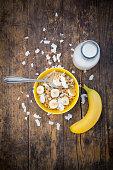 Bowl of granola, banana slices and coconut flakes
