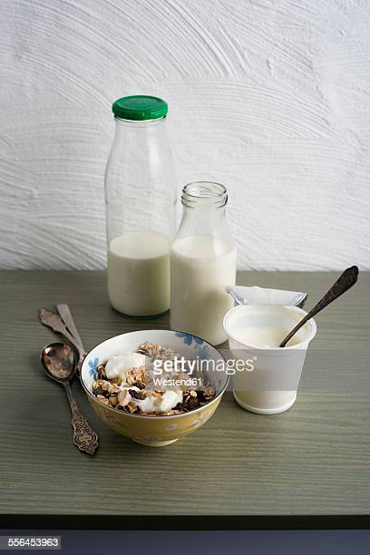 Bowl of granola, bottles of milk and cup of natural yoghurt