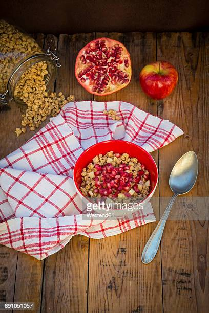 Bowl of granola with pomegranate seed and red apple on wood