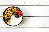 bowl of granola with yogurt, fresh berries, strawberry on wood table.