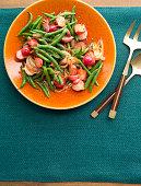 Bowl of green bean & radish salad in orange juice