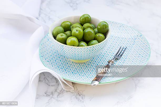 Bowl of green olives and fork on plate and white marble