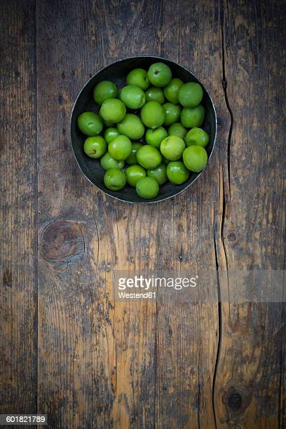 Bowl of green olives on dark wood