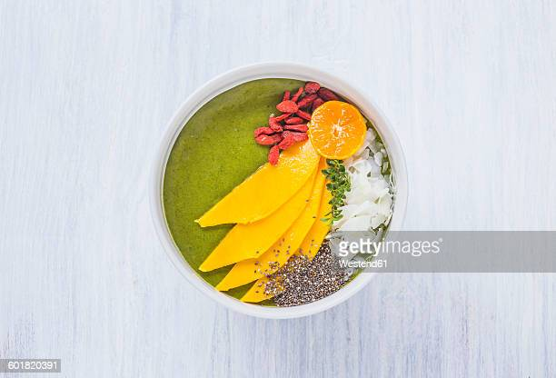 Bowl of green smoothie with topping