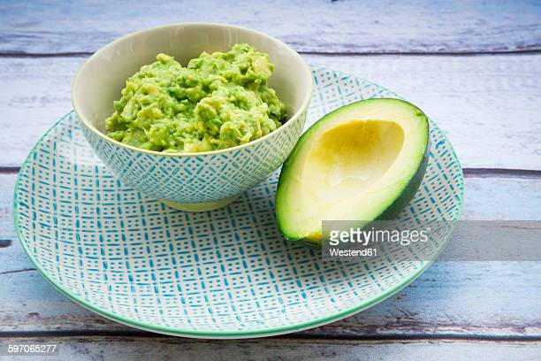 Bowl of Guacamole and half of an avocado on a plate