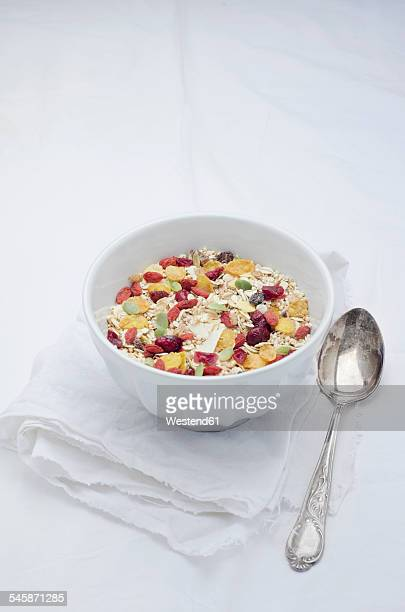 Bowl of homemade muesli with cereals, berries, quinoa grains and coconut flakes on white cloth