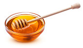 Honey stick and bowl of pouring honey isolated on white background with clipping path