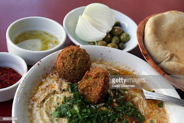 A bowl of hummous is served with olive oil falafel balls and sprinkled with chopped parsley alongside freshbaked pita bread olives a fresh onion red...