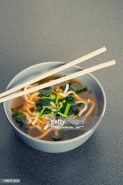 A bowl of Japanese udon noodle soup, algae, chives and chopsticks