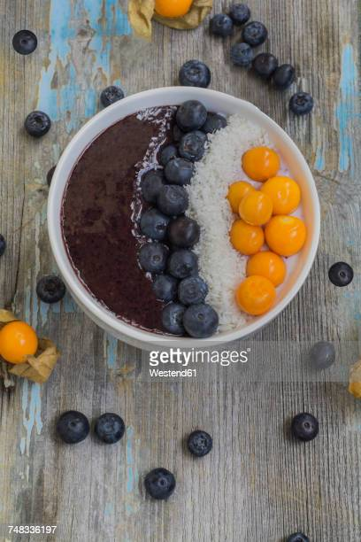 Bowl of joghurt with blueberry mush, coconut flakes, physalis and blueberries