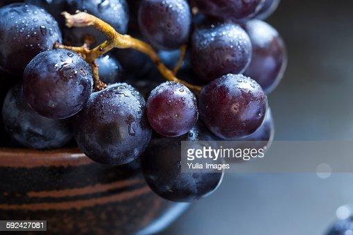 Bowl of juicy ripe black grapes
