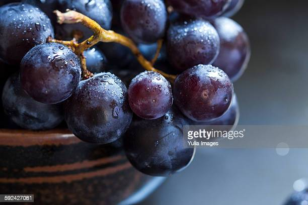 Bowl of juicy ripe black grapes