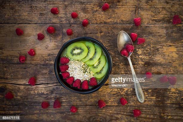 Bowl of kiwi apple rocket smoothie with chia seed, popped amarant, kiwi slices and raspberries