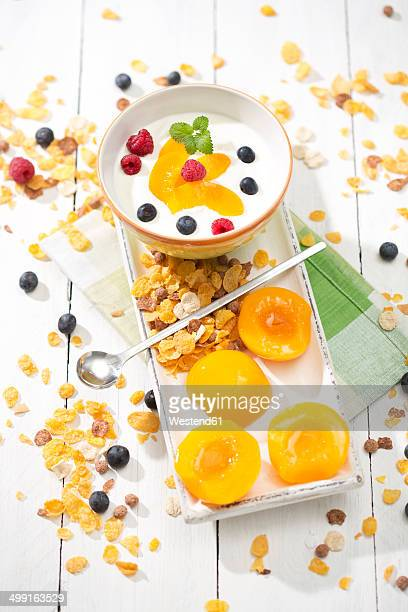 Bowl of lactose-free yogurt with pieces of peach, raspberries, blueberries and cereals on white wooden table