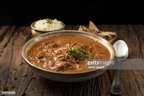 A Bowl Of Lamb Curry Served With Naan Bread And Rice.