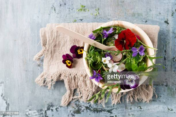 Bowl of leaf salad with red radishes, cress and edible flowers