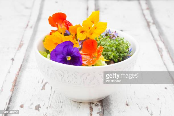 Bowl of leaf salad with various edible flowers