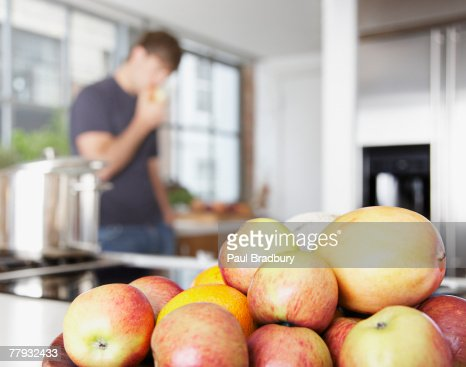 Bowl of mangos and nectarines with man in background eating : Stock Photo