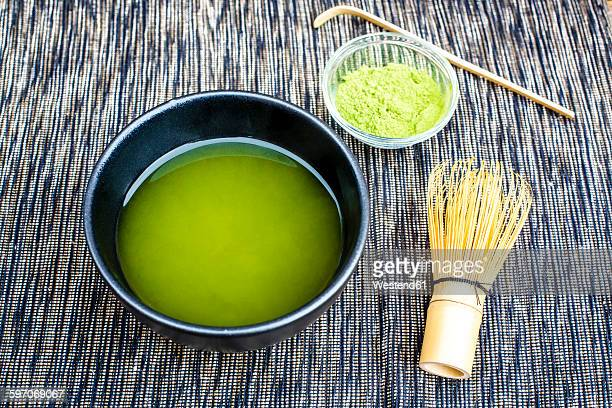 Bowl of matcha tea, matcha powder and tea whisk