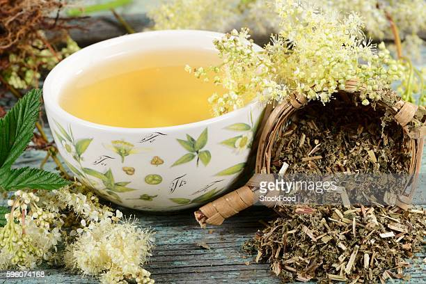 A bowl of meadowsweet tea and tea leaves in a tea strainer