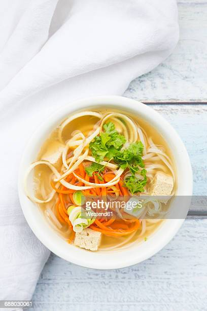 Bowl of miso soup with organic tofu, carrot noodles, parsnip, leek, glass noodles and parsley