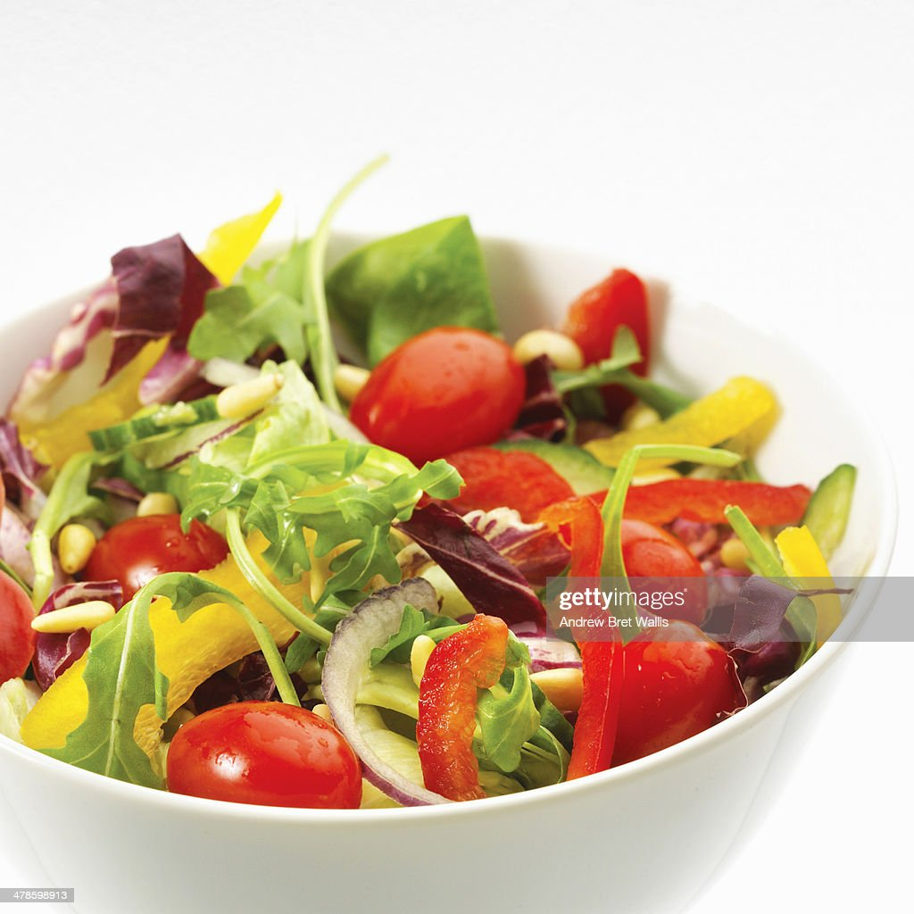 Bowl of mixed salad against white