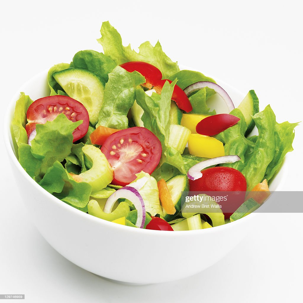 Bowl of mixed salad vegetables against white