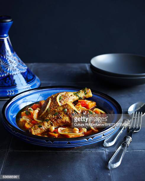 Bowl of moroccan chicken with vegetables and herb garnish