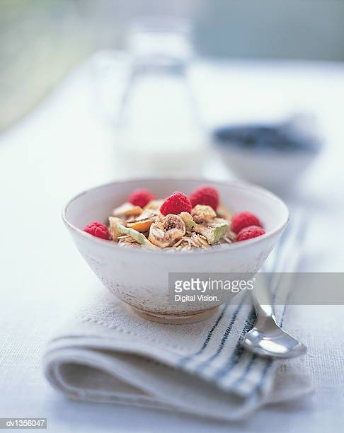 Bowl of Muesli and Raspberries on a Table With a Napkin and a Spoon