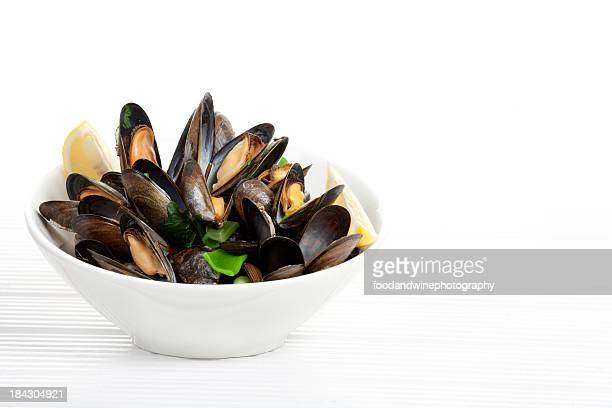 A bowl of mussels garnished with lemons on a white table