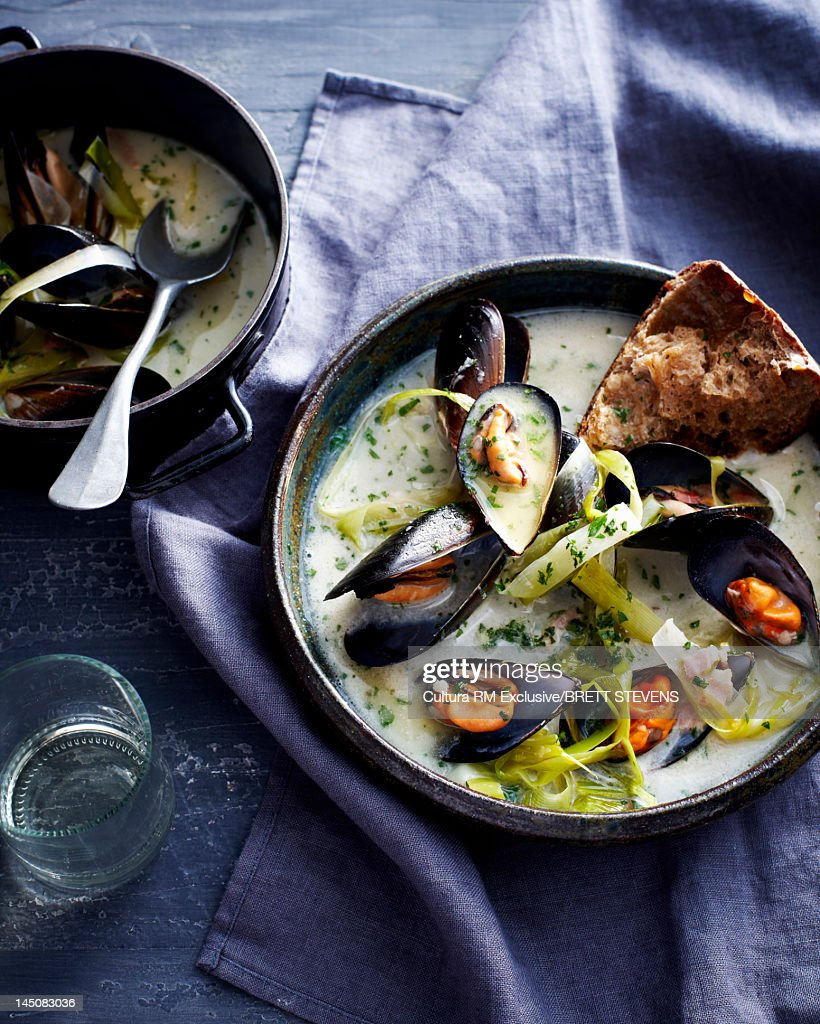 Bowl of mussels in soup with bread