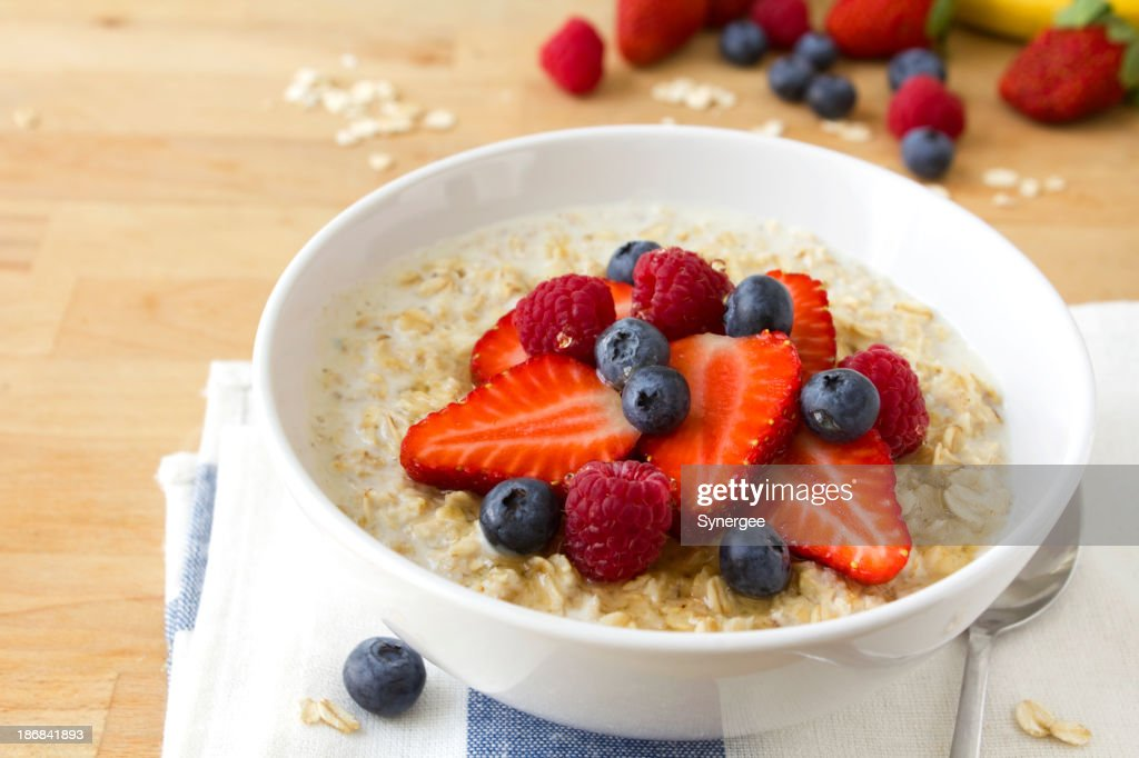 A bowl of oatmeal with blue berries and strawberries : Stock Photo