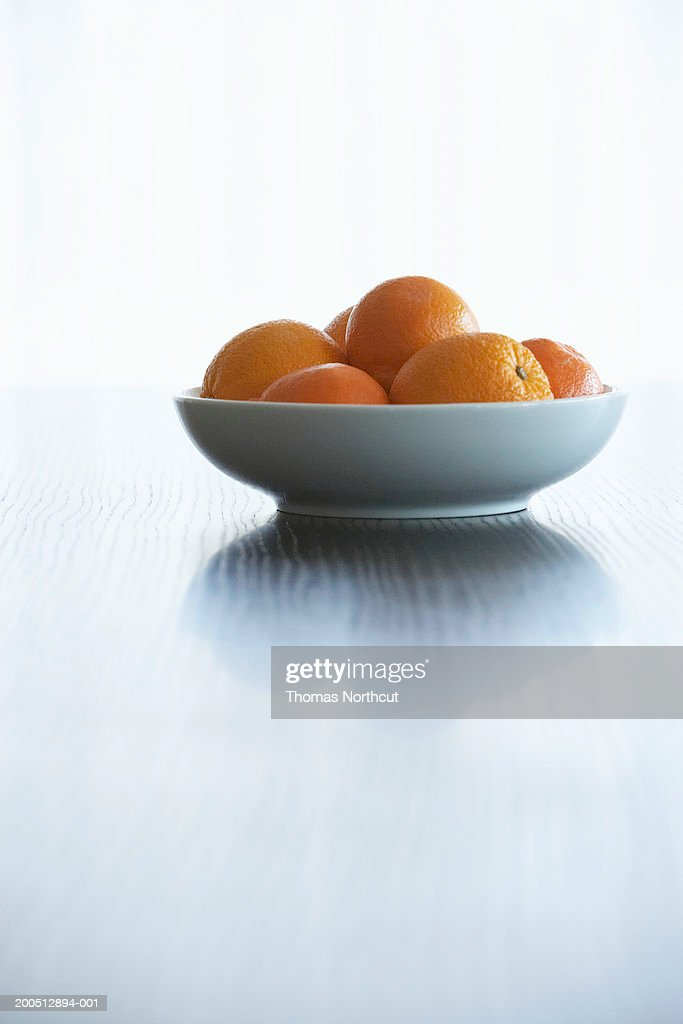 Bowl of oranges atop dining table : Stock Photo