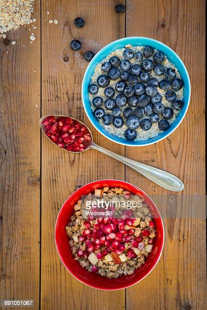 Bowl of overnight oats with blueberries and bowl of granola with pomegranate seed and red apple