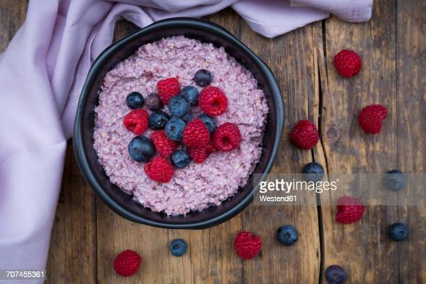 Bowl of overnight oats with blueberries and raspberries on wood