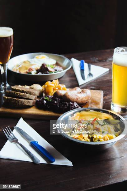 Bowl of pasta, cheese on cutting board and beer on table