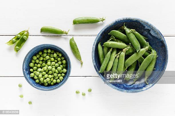 Bowl of pea pods and bowl of peas on white wood, elevated view