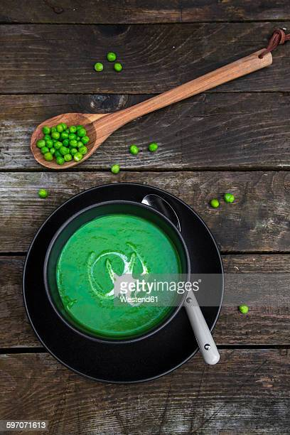 Bowl of pea soup, peas on wooden spoon