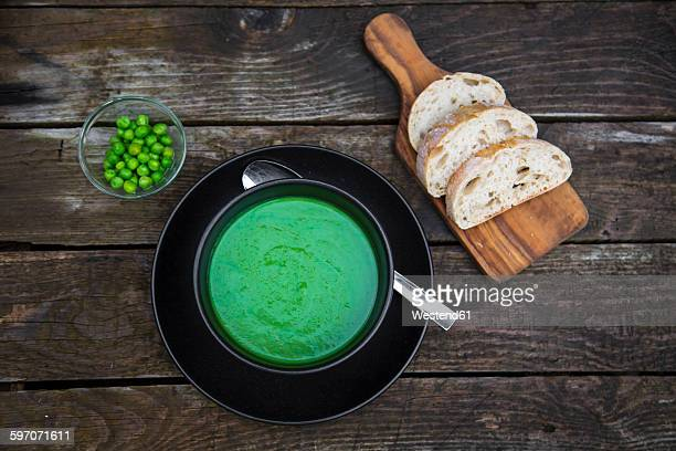 Bowl of pea soup, white bread on chopping board